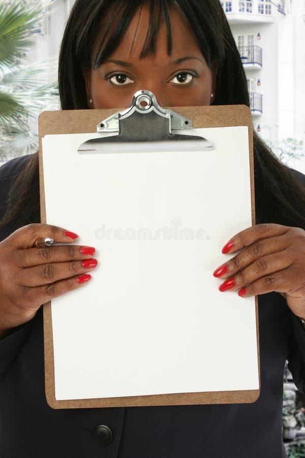 Frau mit unbelegtem Klemmbrett an der Hotel-Vorhalle stockfoto