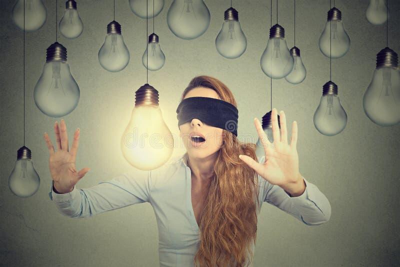 Frau mit verbundenen Augen, die durch die Glühlampen suchen nach guter Idee geht stockfotografie