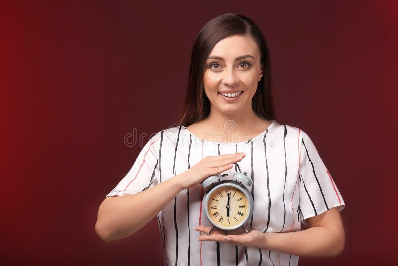 Frau mit Wecker auf Farbhintergrund Schmutz-Hintergrund f?r Ihre Ver?ffentlichungen lizenzfreie stockfotos