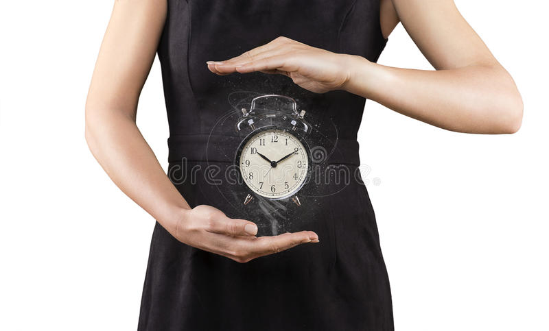 Frau mit Wecker zwischen den Händen, lokalisiert auf weißem, Magie lizenzfreie stockbilder