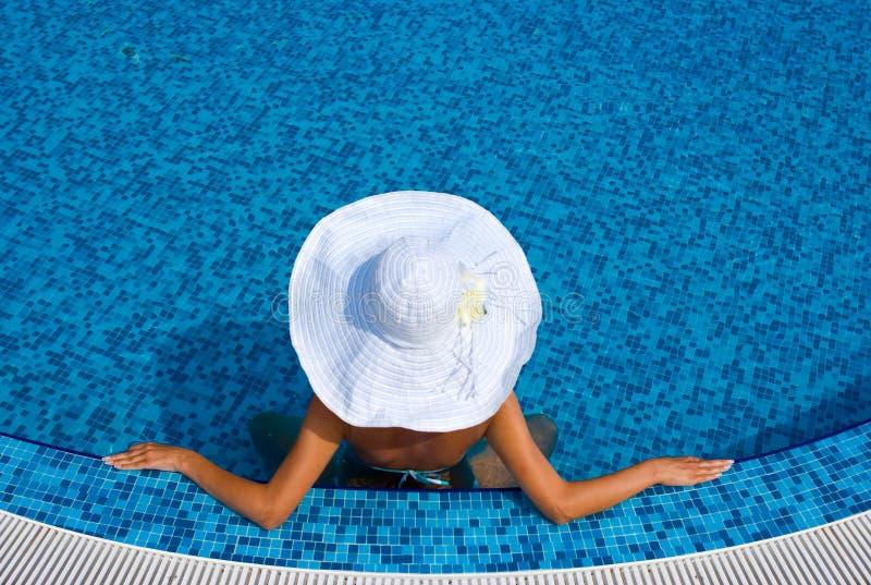 Frau mit weißem Hut im Swimmingpool stockbilder