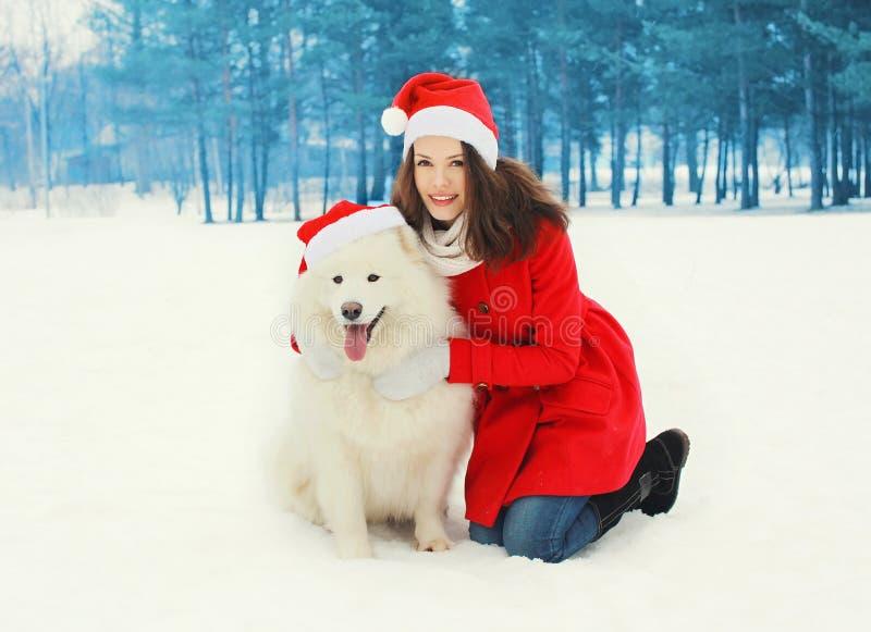 Frau mit weißem Samoyedhund tragende rote Hüte einer Sankt im Winter lizenzfreie stockfotos