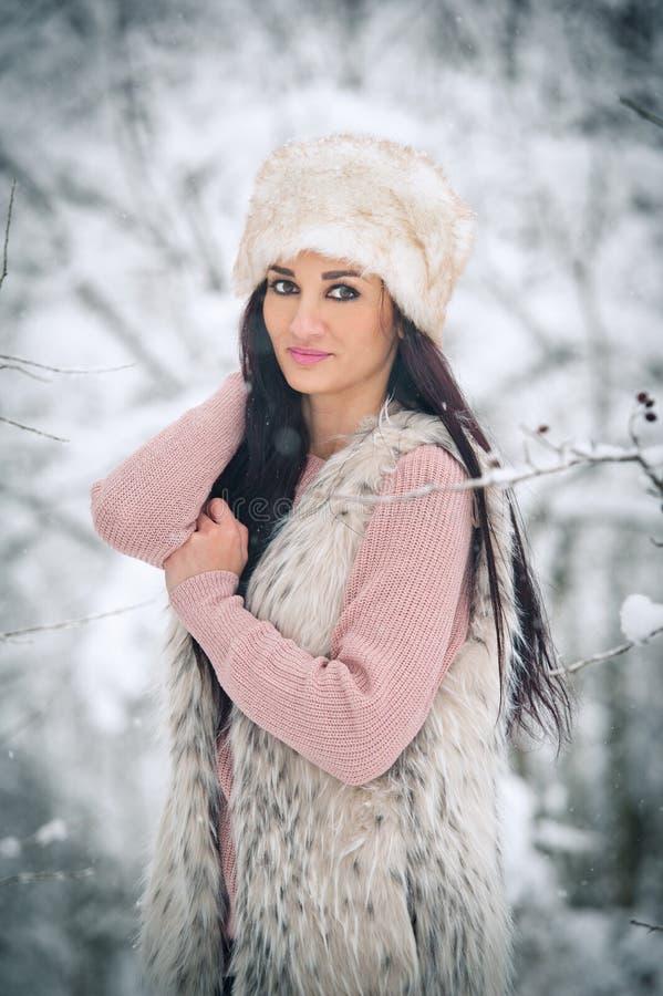 Frau mit weißer Pelzmütze und Schaffell, die die Winterlandschaft in der Waldseitenansicht der glücklichen Brunettemädchenaufstel lizenzfreie stockbilder