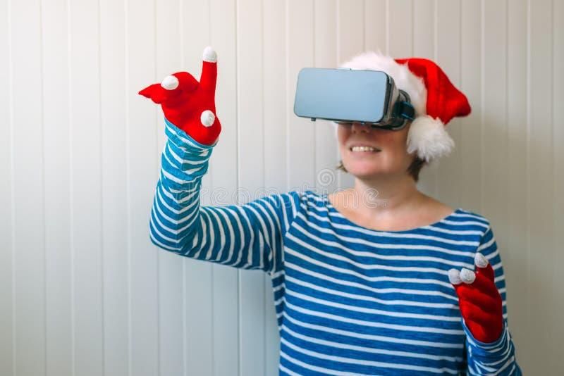 Frau mit Weihnachts-Santa Claus-Hut und VR-Kopfhörer lizenzfreie stockbilder