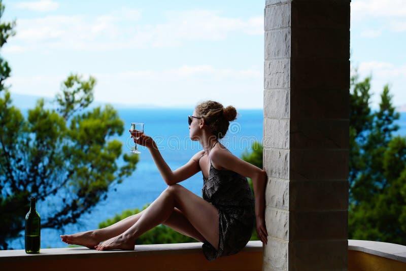 Frau mit Weinglas auf Balkon lizenzfreies stockbild