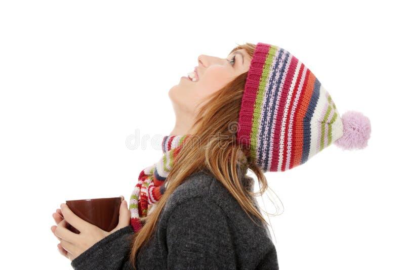 Frau mit Winterschutzkappe etwas trinkend heiß lizenzfreies stockbild