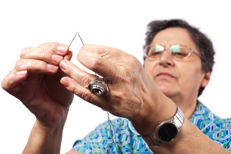 Frau mit Zeichenkette und Nadel lizenzfreie stockbilder