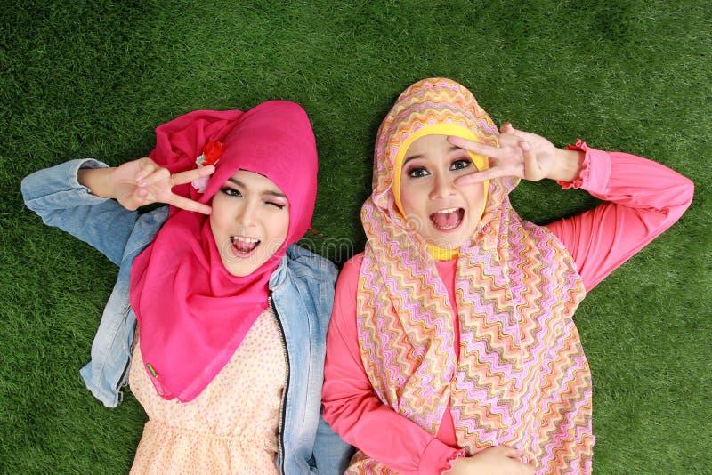 Frau mit zwei Moslems, die auf Gras liegt stockbild