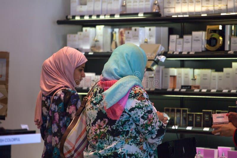 Frau mit zwei Moslems im Parfümshop lizenzfreie stockbilder