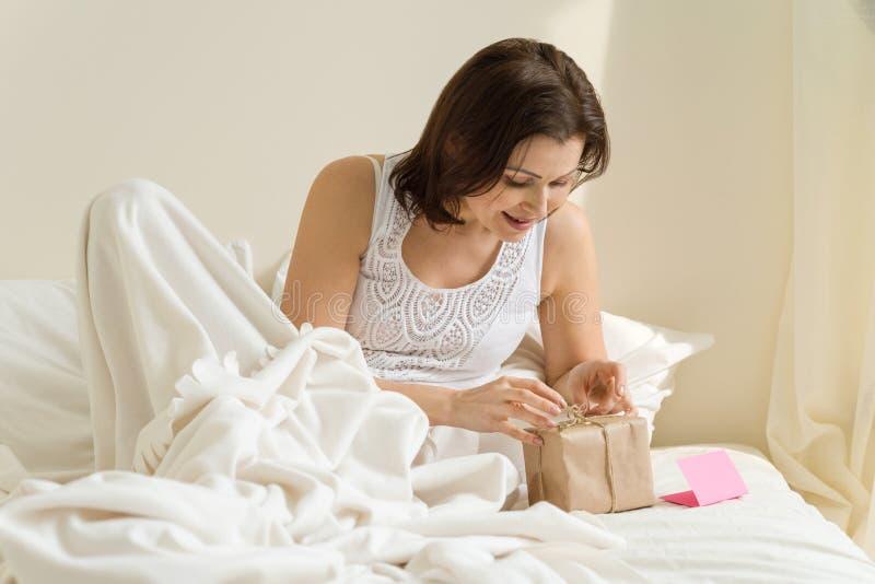 Frau morgens im Bett genießt Geschenk stockfotos