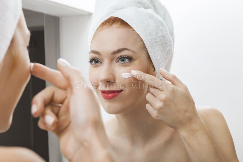 Frau nach der Dusche, die Creme auf ihrem Gesicht aufträgt stockbilder