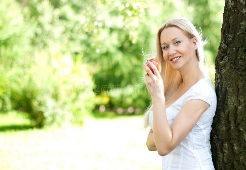 Frau nahe dem Baum mit Apfel lizenzfreie stockfotos