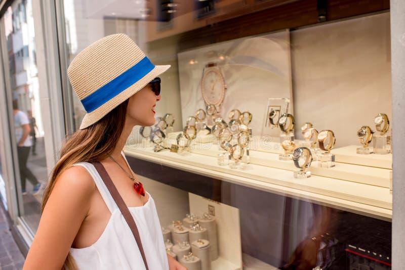 Frau nahe dem Schaukasten mit Uhren lizenzfreies stockfoto