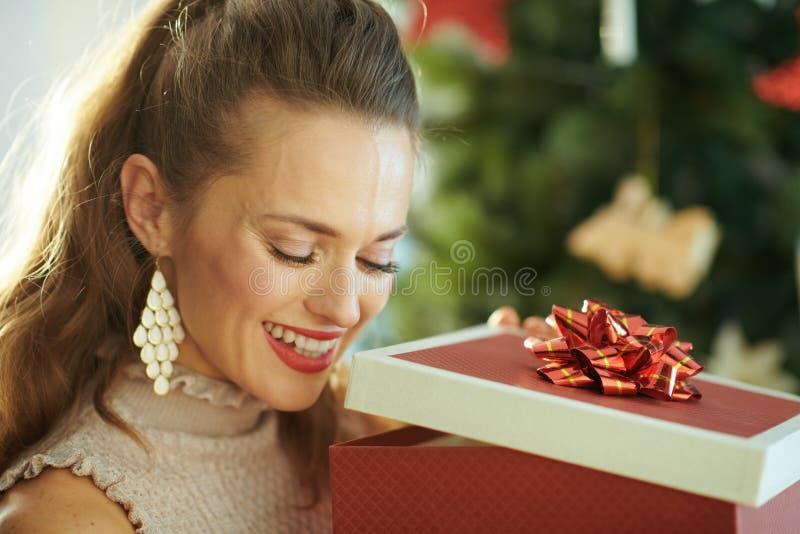 Frau nahe dem Weihnachtsbaum, der innerhalb des Weihnachtspräsentkartons schaut stockfotos