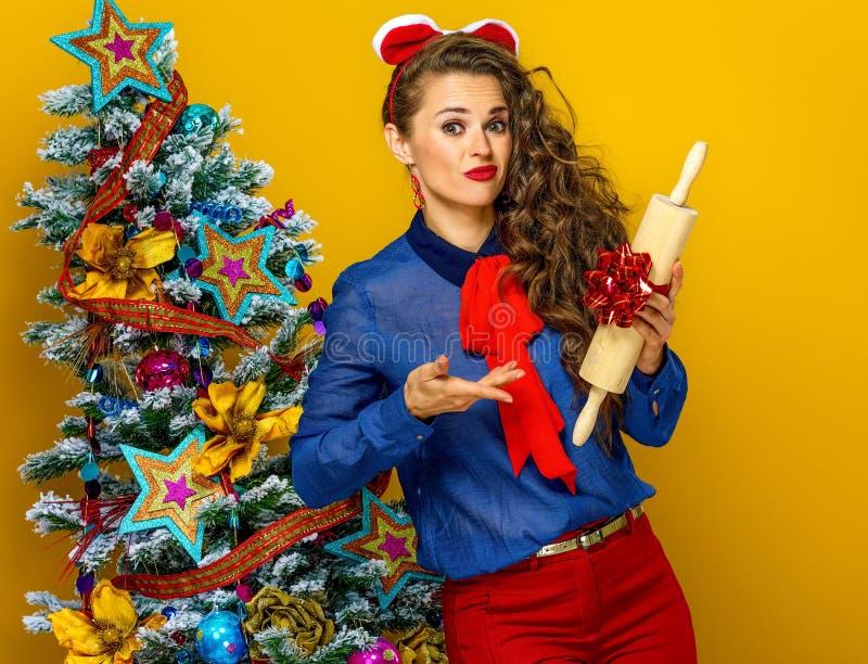 Frau nahe dem Weihnachtsbaum unglücklich mit Geschenk lizenzfreie stockfotografie