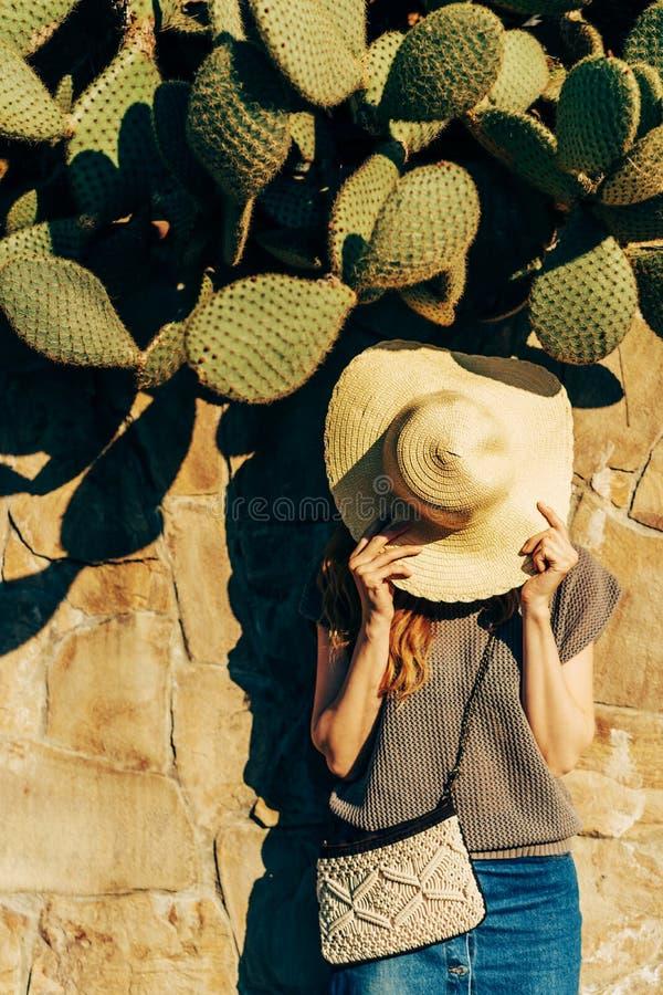 Frau nahe einem Steinzaun mit Kakteen lizenzfreies stockfoto