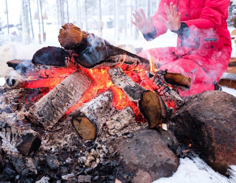 Frau nahe Feuer in der Winterlandschaft stockbild