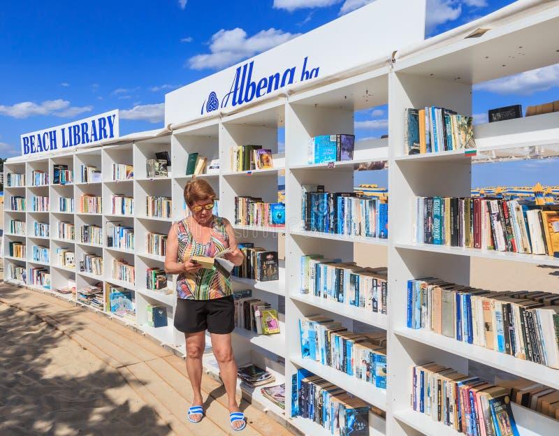 Frau nahe freier Strandbibliothek öffnete sich am Erholungsort Schwarzen Meers von lizenzfreies stockfoto