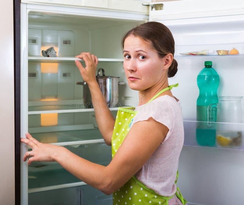 Frau nahe leerem Kühlschrank lizenzfreie stockfotos