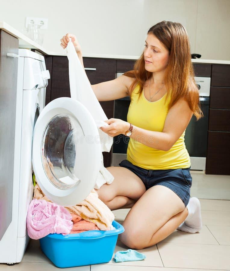 Frau nahe Waschmaschine lizenzfreie stockbilder