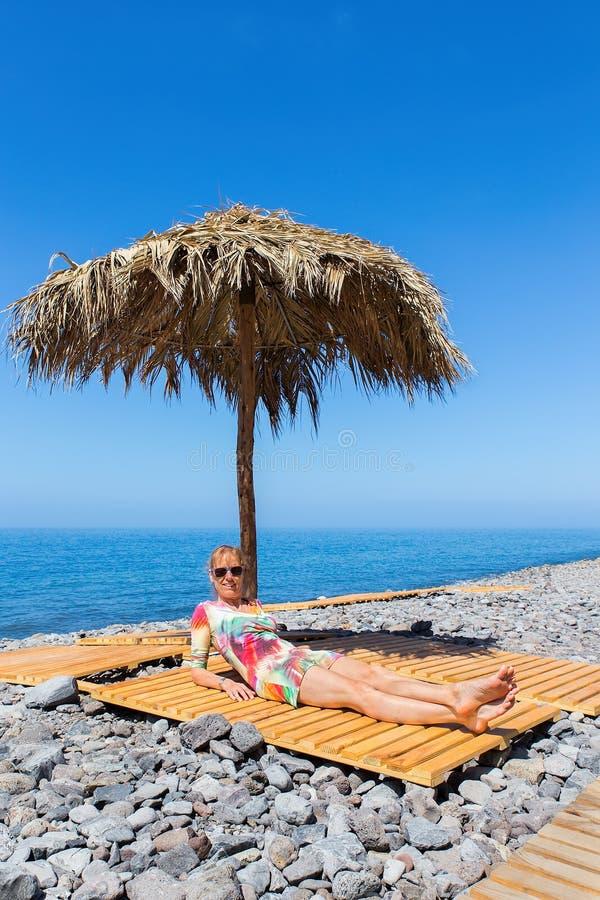 Frau nimmt als Tourist auf steinigem europäischem Strand ein Sonnenbad lizenzfreie stockfotografie