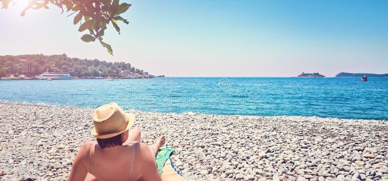 Frau nimmt bräunende Meerstrand Zanjic Adriatik Montenegro-Halbinsel Lustica ein Sonnenbad lizenzfreie stockfotos