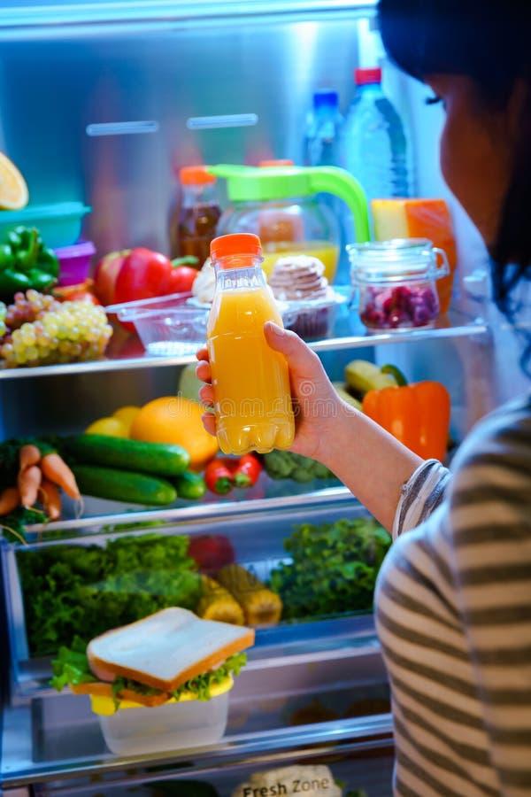 Frau nimmt den Orangensaft vom offenen Kühlschrank stockbild
