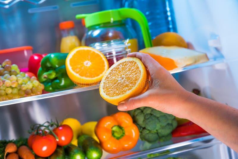 Frau nimmt die Orange vom offenen Kühlschrank lizenzfreie stockfotografie