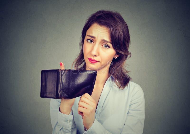 Frau ohne Geld Traurige Geschäftsfrau, die leere Geldbörse hält lizenzfreies stockbild
