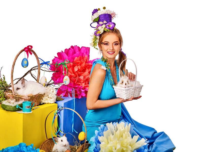 Frau in Ostern-Art, die Kaninchen und Blumen im Korb hält lizenzfreies stockfoto