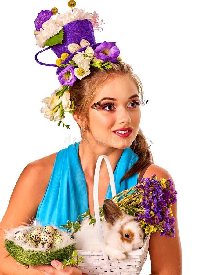 Frau in Ostern-Art, die Kaninchen und Blumen im Korb hält lizenzfreie stockbilder