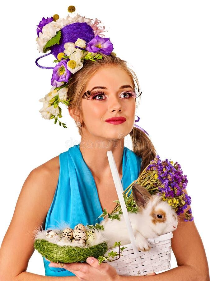 Frau in Ostern-Art, die Kaninchen und Blumen im Korb hält lizenzfreies stockbild