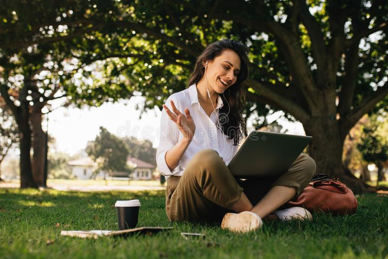 Frau am Park, der einen Videokonferenzanruf auf ihrem Laptop hat stockbild