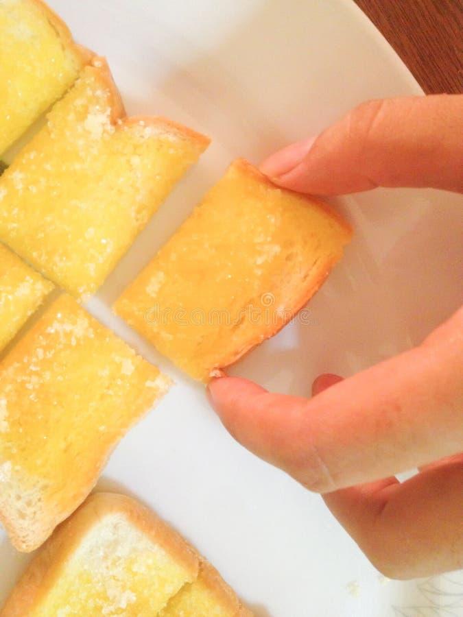 Frau pflücken herauf Butterhonigtoast-Zuckerbelag mit der Hand stockfotografie