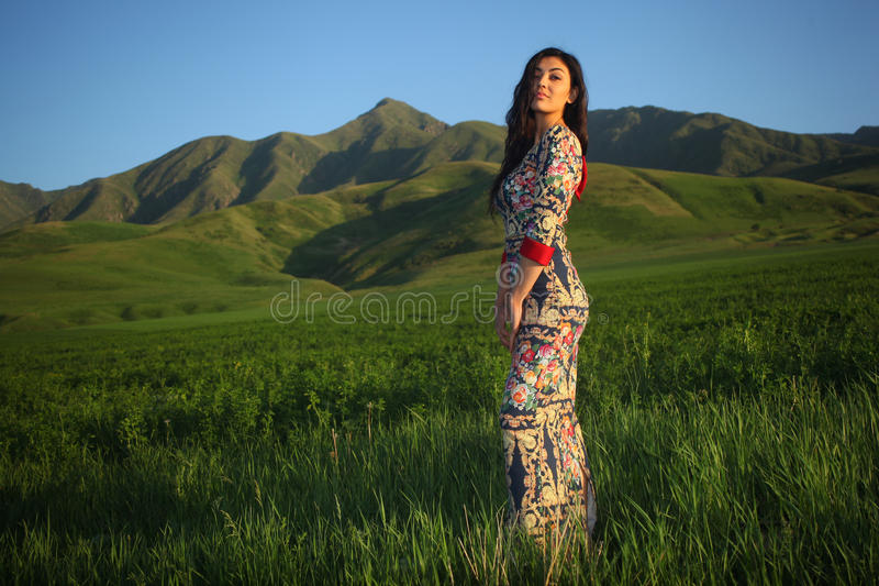 Frau in Platte bei Sonnenuntergang auf einem Gebiet auf einem Hintergrund von Bergen stockfotografie