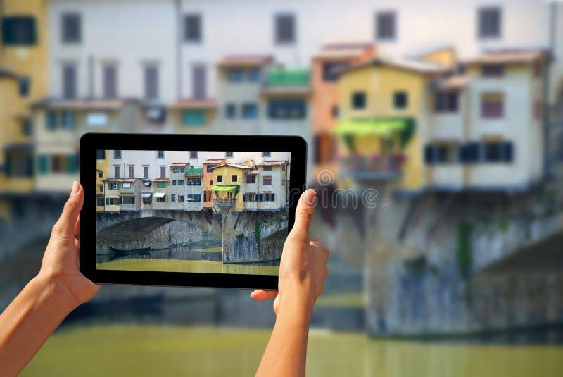 Frau Ponte Vecchio, die Fotos auf einer Tablette macht lizenzfreies stockfoto