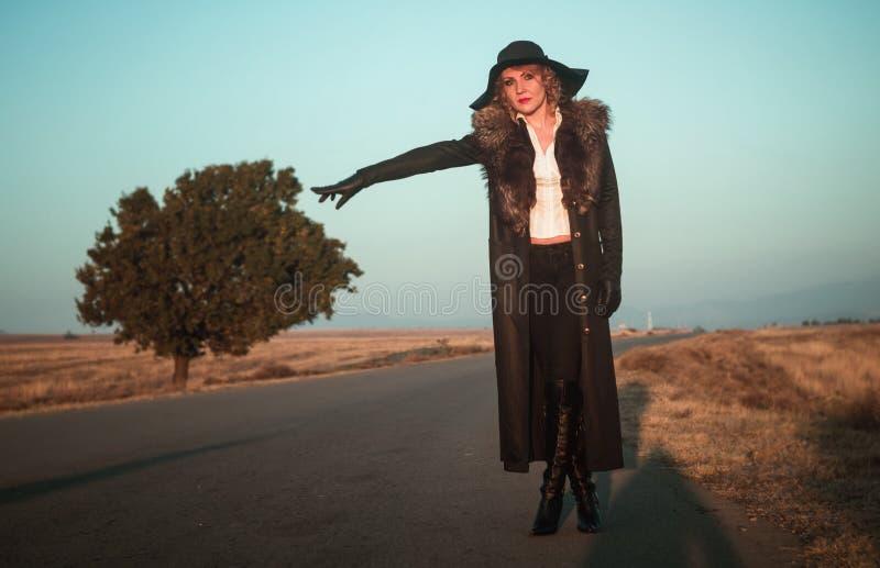 Frau ritt an das Fangen einer Fahrt lizenzfreie stockbilder