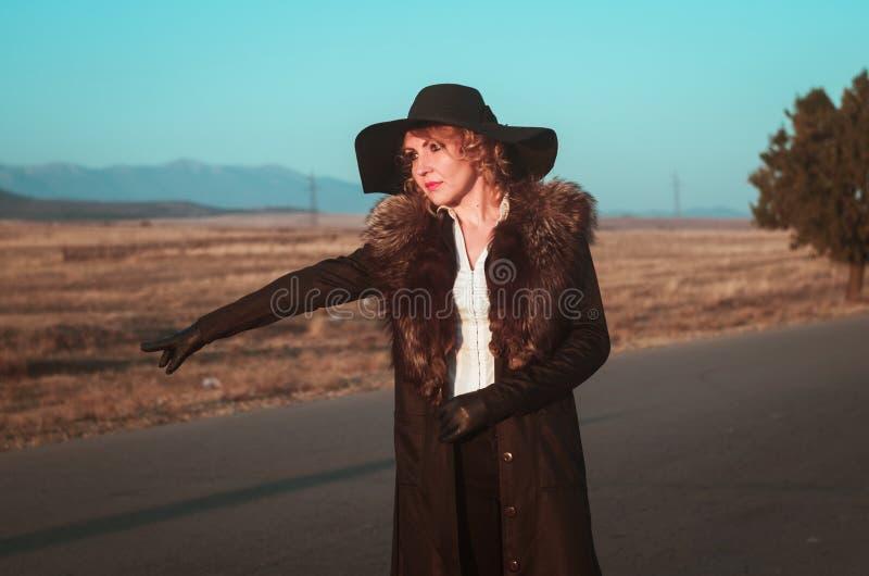 Frau ritt an das Fangen einer Fahrt stockfotografie