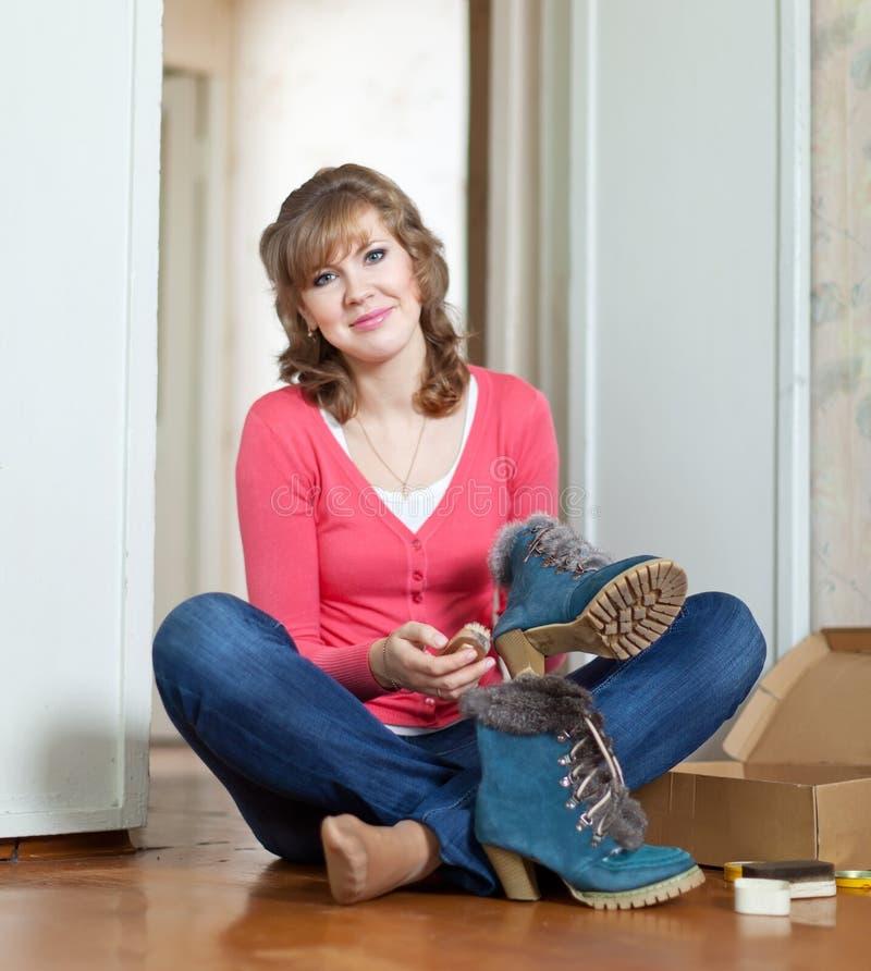 Frau säubert Fußbekleidung stockbild