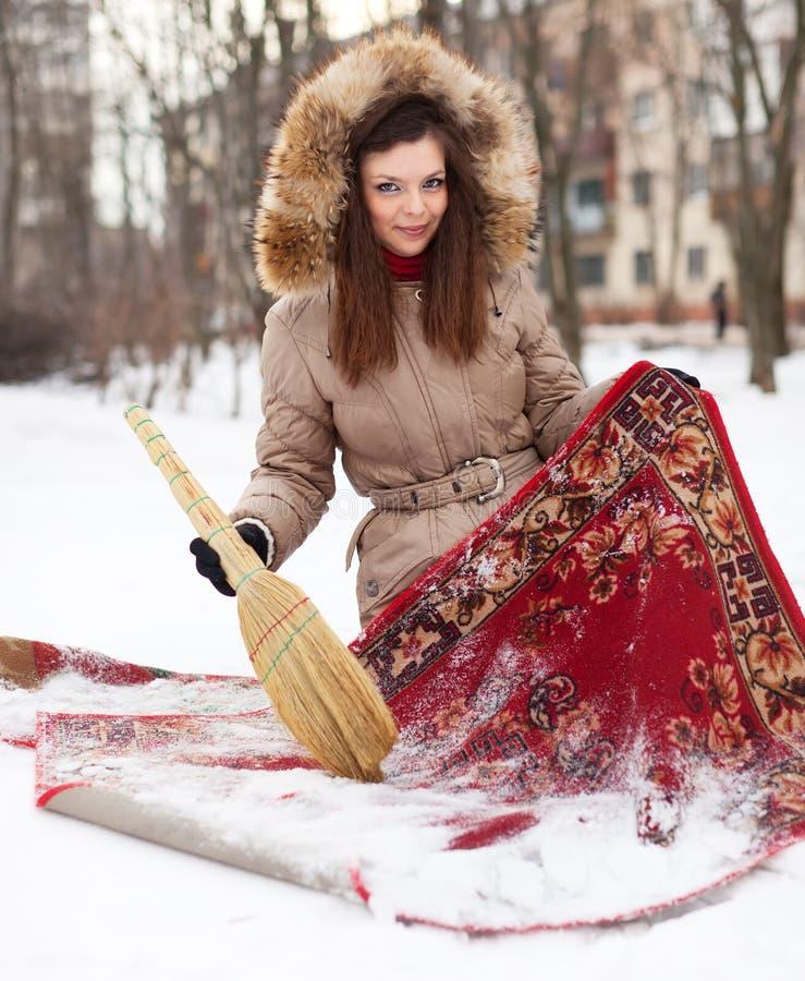 Frau säubert roten Teppich mit Schnee lizenzfreie stockfotografie