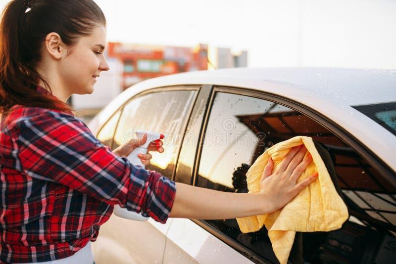 Frau säubert vorderes Glas des Autos mit Spray lizenzfreies stockfoto
