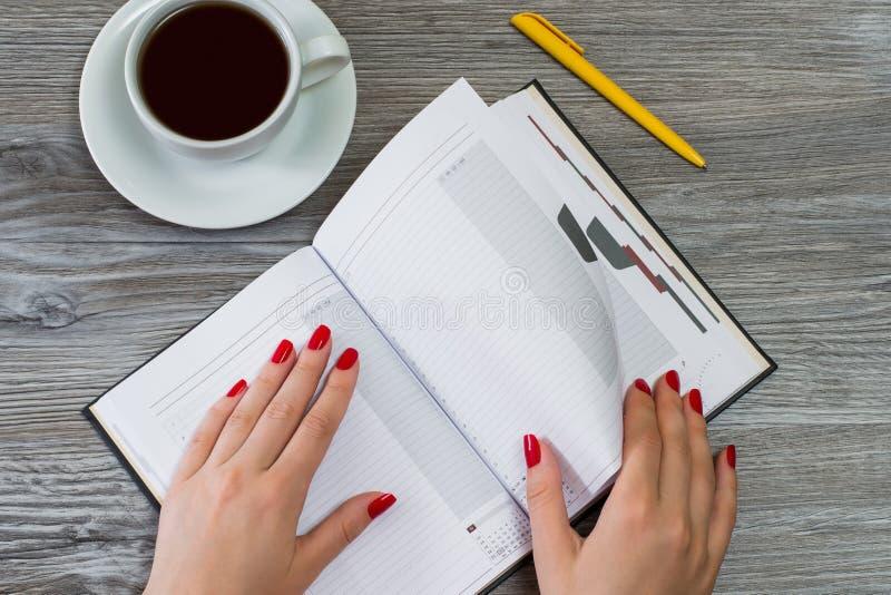 Frau ` s übergibt das Drehen einer Seite in einem Notizbuch Tasse Tee und einen Stift lizenzfreie stockfotografie