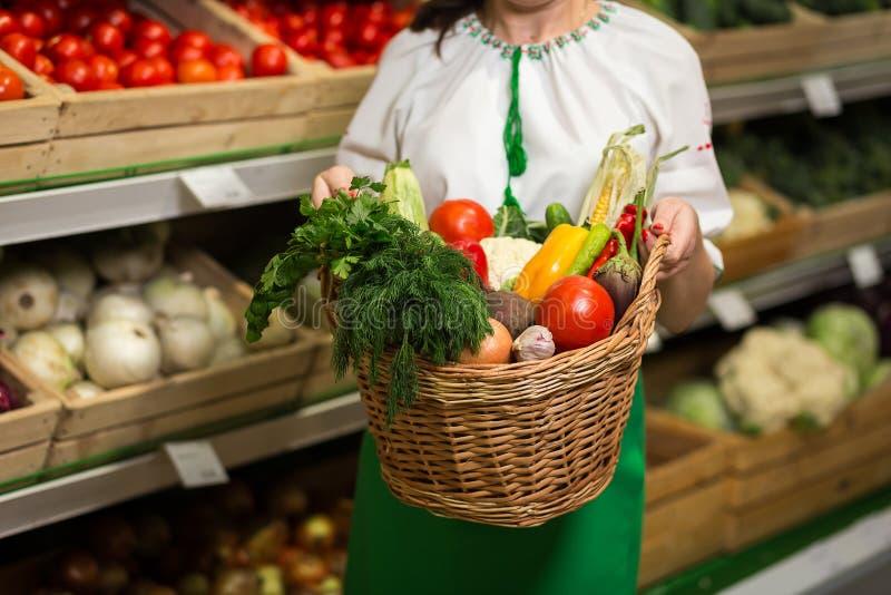 Frau ` s übergibt das Halten eines Korbes der Gemüseernte im Markt lizenzfreies stockbild