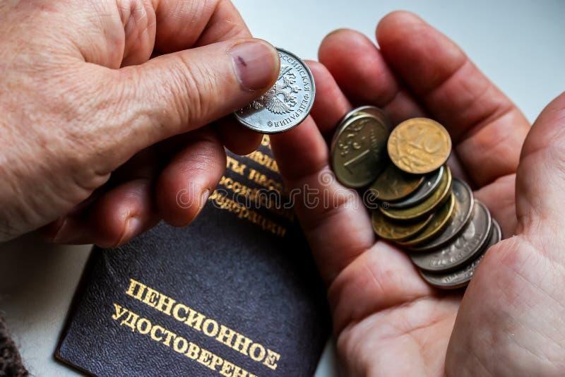 Frau ` s übergibt das Halten von russischen Münzen über dem Pensionszertifikat lizenzfreie stockbilder