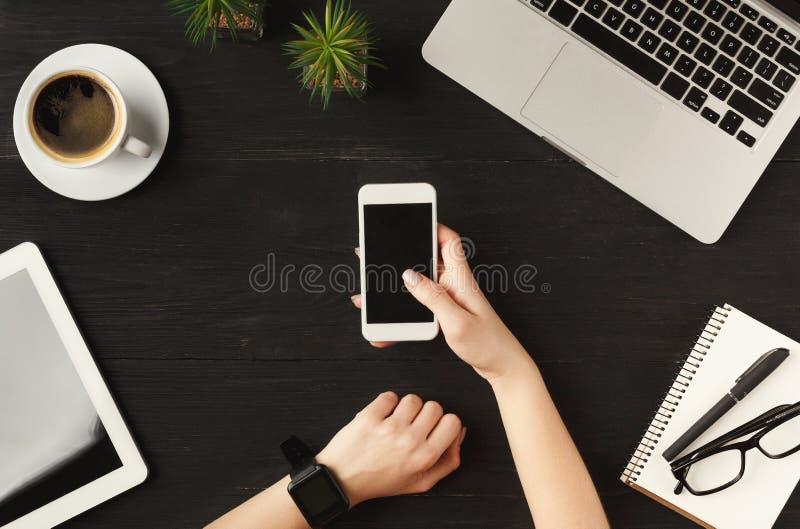 Frau ` s übergibt das Halten von Smartphone, Draufsicht stockfotografie