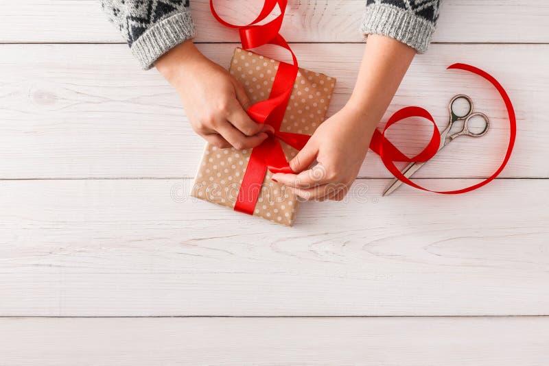 Frau ` s übergibt die Verpackung des Weihnachtsfeiertags vorhanden mit rotem Band lizenzfreie stockbilder