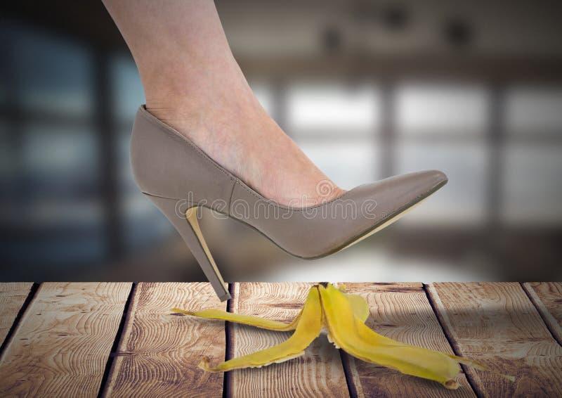 Frau ` s Fuß ungefähr zum Schritt auf Bananenschale und zum Beleg irrtümlich auf Holz lizenzfreie stockbilder