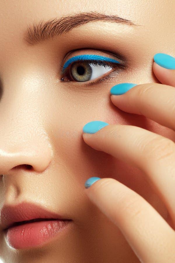 Frau ` s Gesicht mit klarem Make-up und buntem Nagellack stockbilder