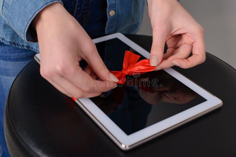 Frau ` s Hände binden digitale weiße Tablette mit rotem Band Sie bereitet sich für Auflagen-Computer lapto pda Technologie der Wi lizenzfreies stockbild