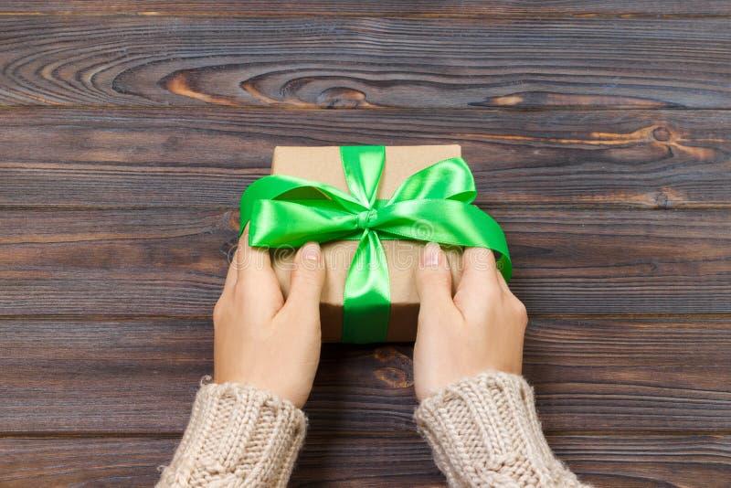 Frau ` s Hände geben eingewickeltes handgemachtes Geschenk des Valentinsgrußfeiertags im Kraftpapier mit grünem Band Präsentkarto stockbilder